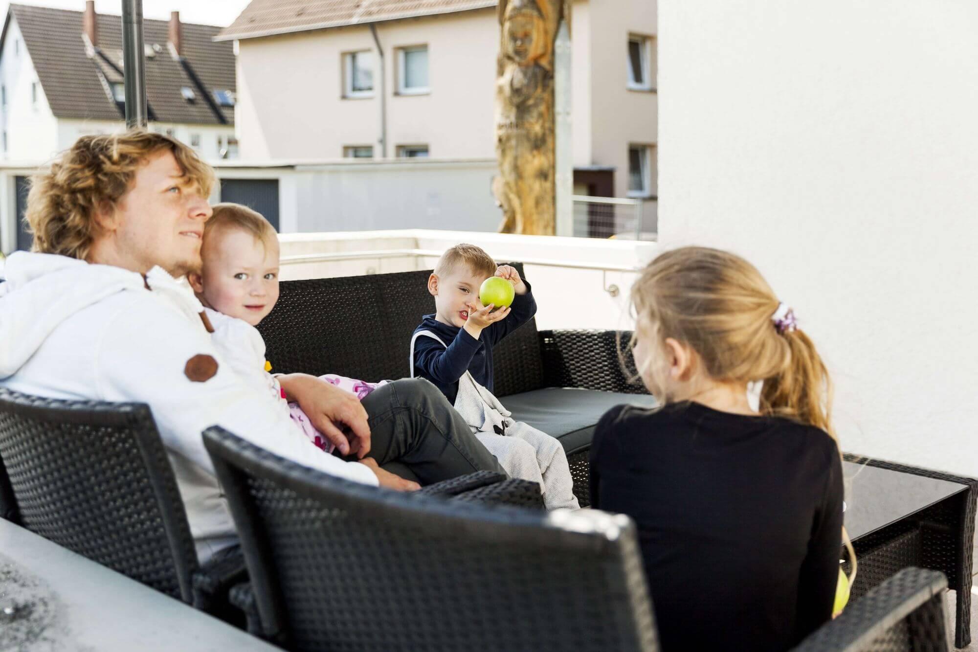 Drei Kinder und ein Erwachsener auf der Sommerterrasse im Eingangsbereich