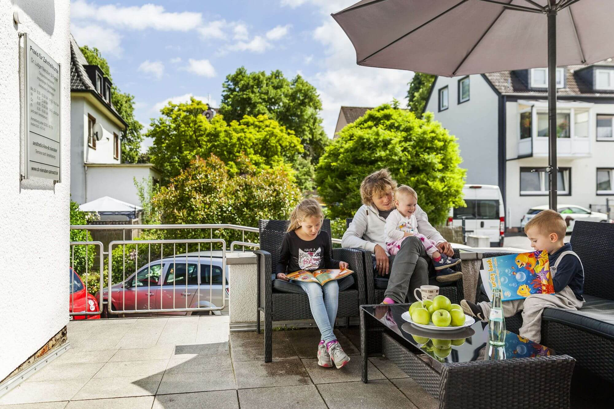 Drei Kinder und ein Erwachsener unter Sonnenschirm auf der Sommerterrasse