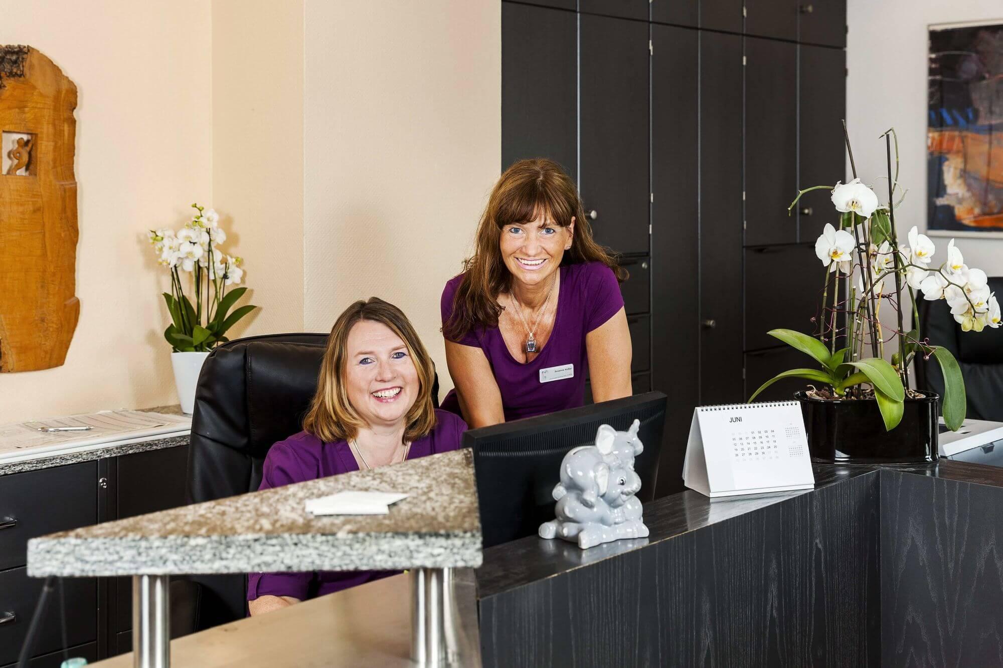 Freundlich lächelnde Mitarbeiterinnen im Empfangsbereich