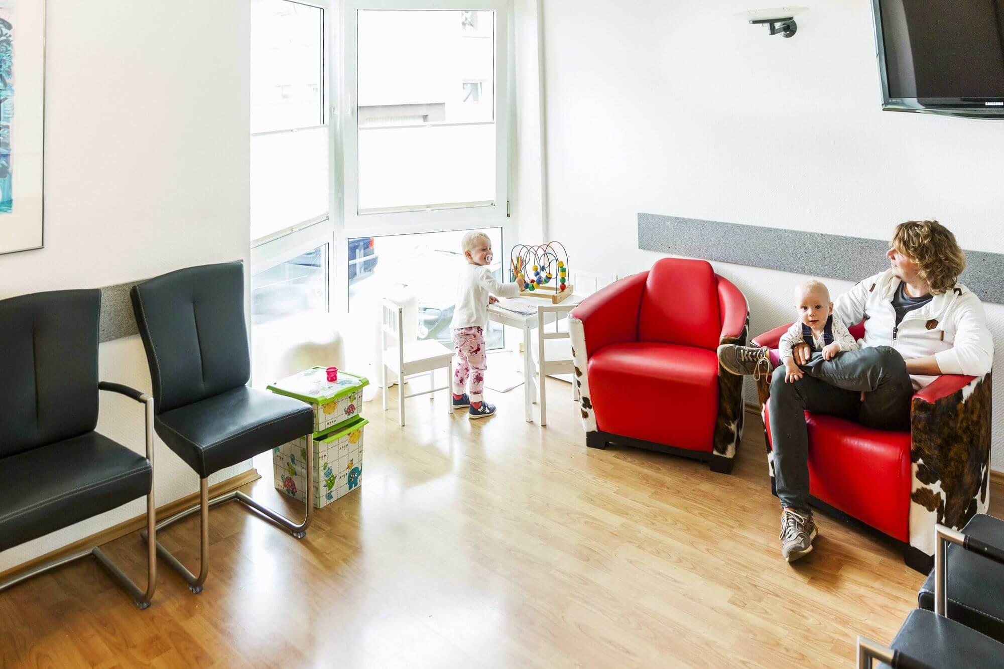 Spielende Kinder und Erwachsene im Wartezimmer