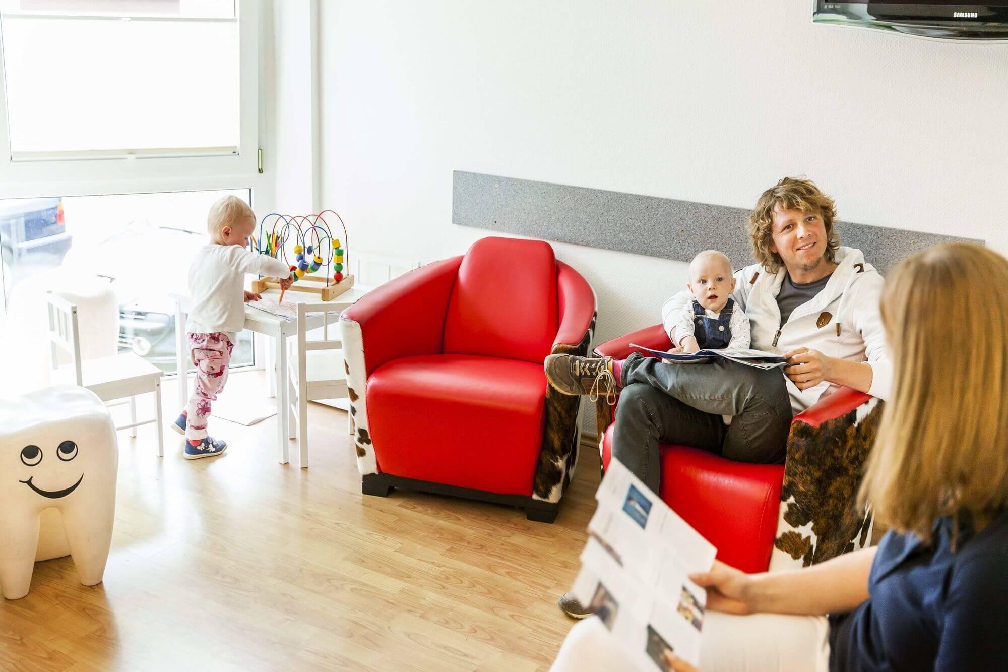 Wartezimmer mit Kindern und sich unterhaltenden Erwachsenen