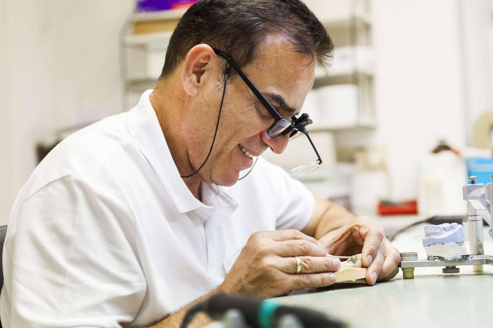 Zahntechniker-Meister mit Spezialbrille bei der Arbeit