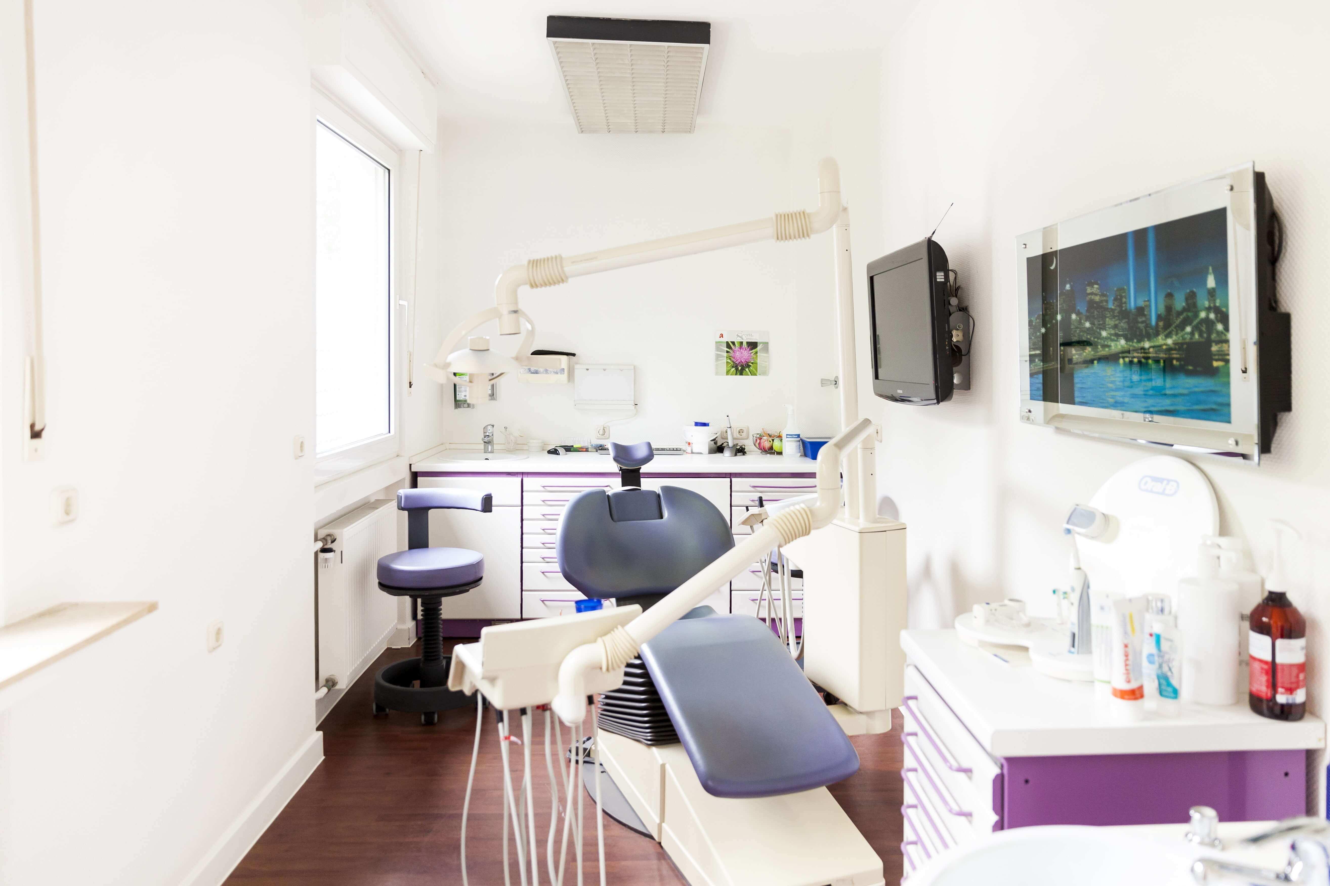 Behandlungszimmer mit Stühlen und Schränken mit violetter Farbnote